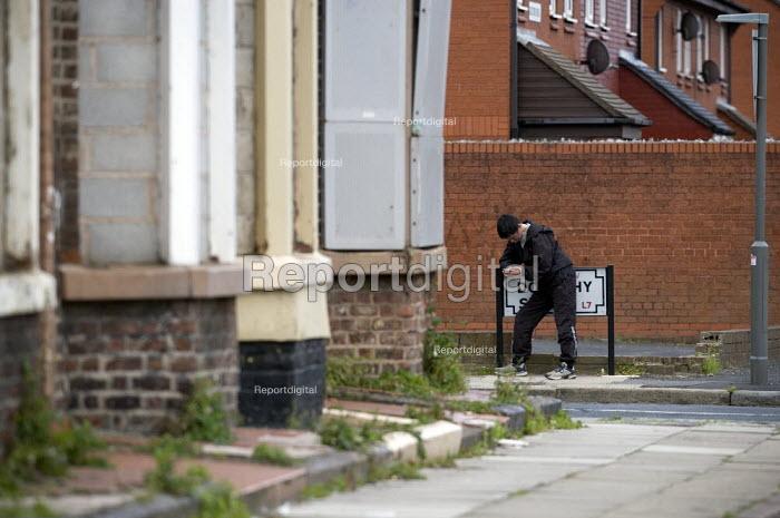 A man texting on a street corner. Kensington, Liverpool - John Harris - 2009-09-14