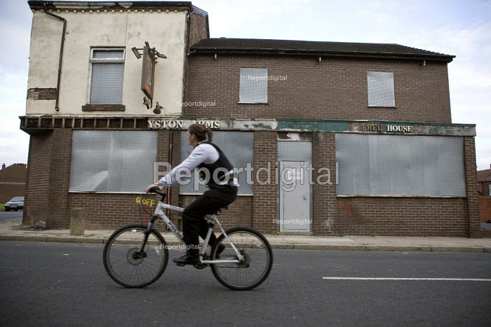 A policewoman patrolling a poor area of Liverpool on her police bicycle. A closed public house, Kensington. - John Harris - 2009-09-14