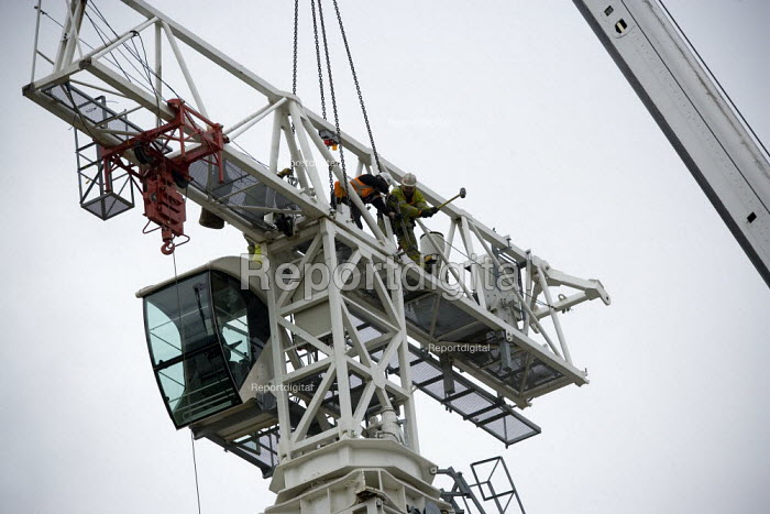 Workers disassemble a tower crane, removing the jib or boom, loosening a bolt by hitting it with sledgehammer, RSC Stratford upon Avon - John Harris - 2009-10-06