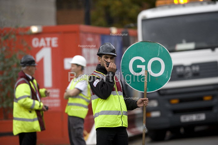 Worker with a radio controlling the traffic flow with manually operated Stop Go temporary traffic control system at the building site entrance. RSC Stratford upon Avon - John Harris - 2009-10-06