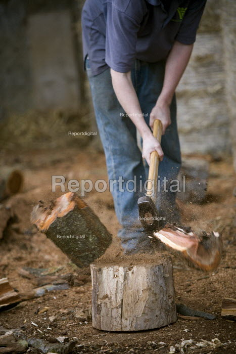 Farmworkers cutting up trees for firewood on a farm in Warwickshire. Chopping with an axe. - John Harris - 2009-10-12