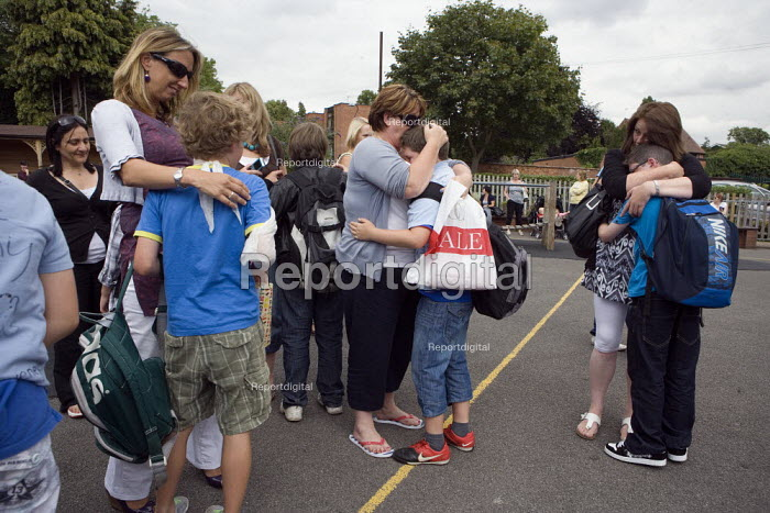 Mother hug and comfort their boys. Emotional scenes in the playground on the last day of term for those leaving at the end of their primary school education. St Gregory's Catholic Primary School, Stratford upon Avon, Warwickshire - John Harris - 2010-07-23