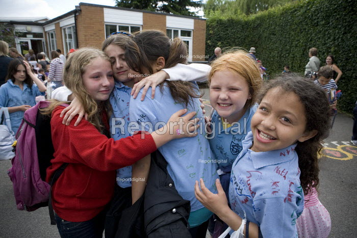Girls hug and comfort each other. Emotional scenes in the playground on the last day of term for those leaving at the end of their primary school education. St Gregory's Catholic Primary School, Stratford upon Avon, Warwickshire - John Harris - 2010-07-23