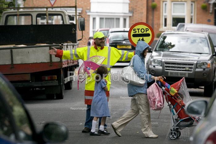 A school crossing patrol warden helping pedestrians to cross the road in safety. - John Harris - 2010-07-17