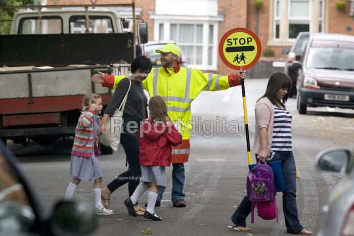 A school crossing patrol warden helping pedestrians to cross the road in safety. - John Harris - 2010-07-17