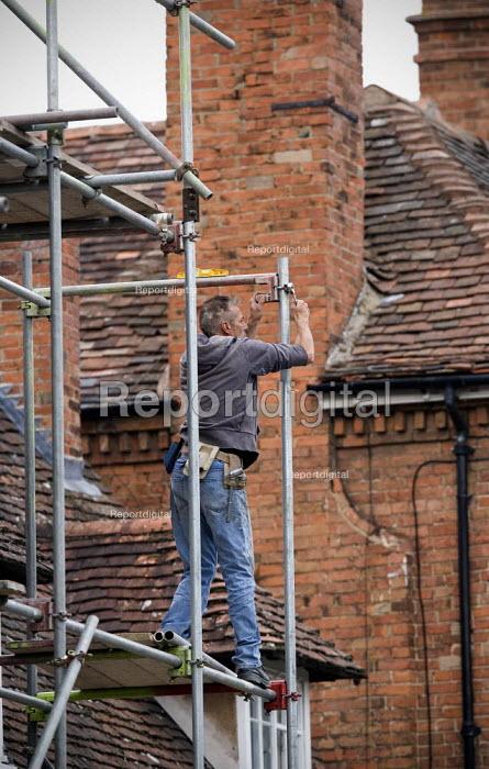 A scaffolder erecting scaffolding around a house. - John Harris - 2010-09-06