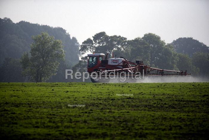 A landworker driving a sprayer, making a pre-emergent pesticide application onto a wheat crop, Warwickshire. - John Harris - 2010-10-08