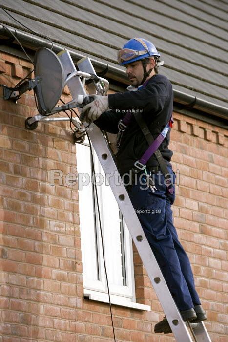 An engineer installing a Sky TV satellite dish onto a house on a housing estate - John Harris - 2010-10-27