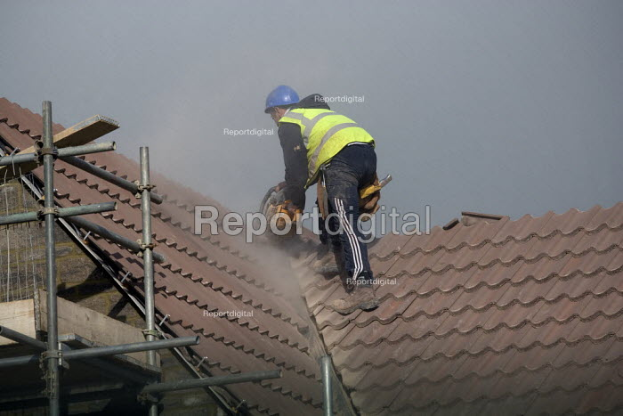 A worker cutting tiles on a roof. New homes being built on an estate, West Wick, Weston-super-Mare - John Harris - 2010-11-10