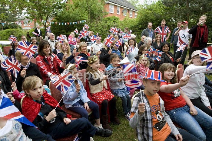 Children and parents at a Street Party watching the Royal Wedding Day on TV and waving union jack flags, Stratford upon Avon, Warwickshire - John Harris - 2011-04-29