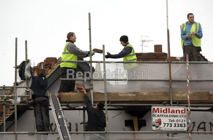 Workers replacing tiles on the roof of a hotel undergoing refurbishment, Stratford-upon-Avon. - John Harris - 2012-01-26