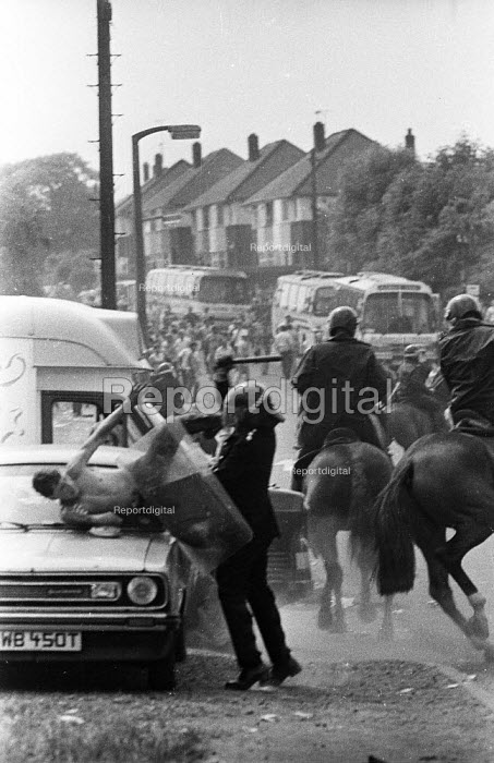 Senior police officer attacking a miner guarding his car. The attempt to prosecute the miner for riot collapsed. Orgreave coking plant Miners strike Sheffield South Yorkshire - John Harris - 1984-06-18