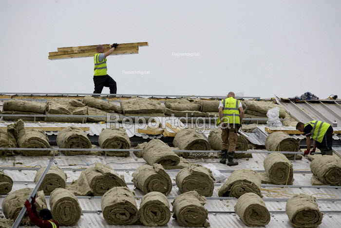 Contractors retrofitting fiberglass roof insulation to a large building. - John Harris - 2012-03-13