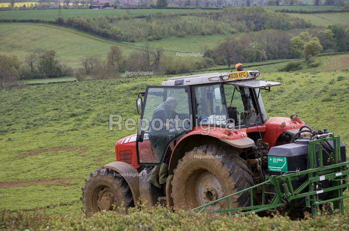A farmworker climbing into his cab. Crop spraying with a tractor and rig on a farm in Oxfordshire - John Harris - 2012-05-21