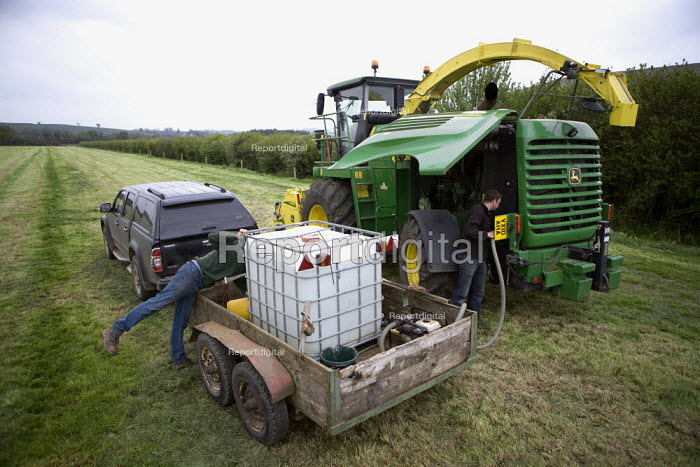 Filling the harvester with an additive mixture including bacteria, enzymes, mold inhibitors, and preservatives to accelerate the fermentation process. Silage making on a farm, Wormleighton, Warwickshire - John Harris - 2012-05-22