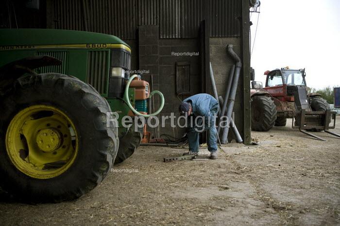 A farmworker maintaining machinery in a farmyard Wormleighton, Warwickshire - John Harris - 2012-05-22