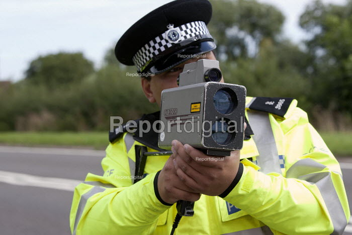 Police officer using a LTI 20:20 Speedscope mobile Speed camera To detect speeding motorists, Warwickshire. - John Harris - 2013-08-21