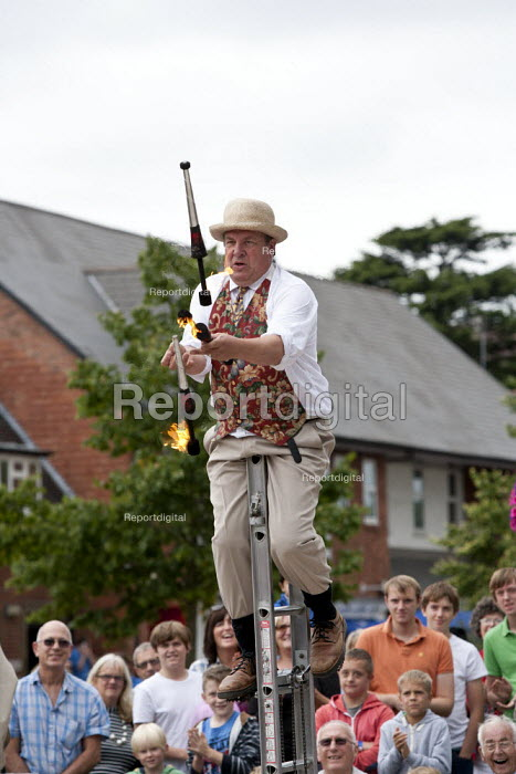 Street entertainers, Juggling fire sticks on a unicycle. Tourists visiting Stratford upon Avon, Warwickshire - John Harris - 2013-08-24