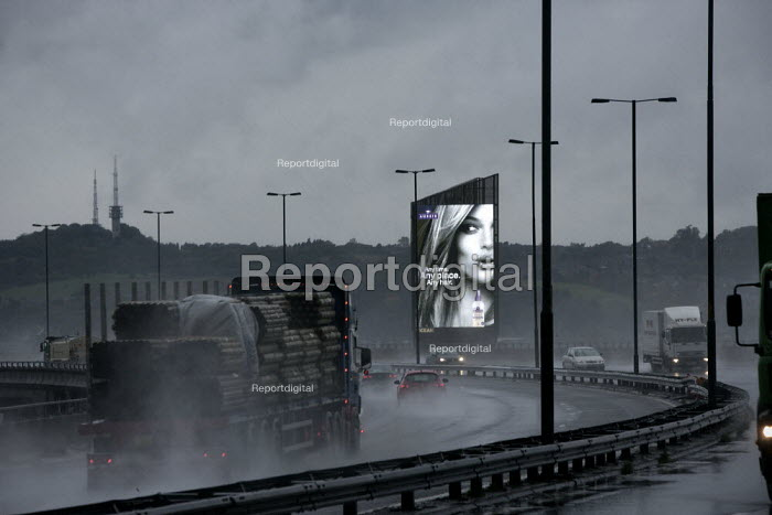 A Woman in an illuminated advertisement for Aussie Miracle Recharge Moisture Infuser Leave-in Conditioner and shampoo beside the M5 motorway, A heavy rain storm has made driving conditions hazardous with poor visibility. West Midlands - John Harris - 2013-10-22