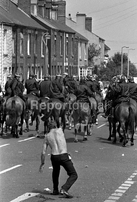 A miner throwing a stone as mounted police move back to police lines after another charge. Orgreave coking works June 1984 - John Harris - 1984-06-18