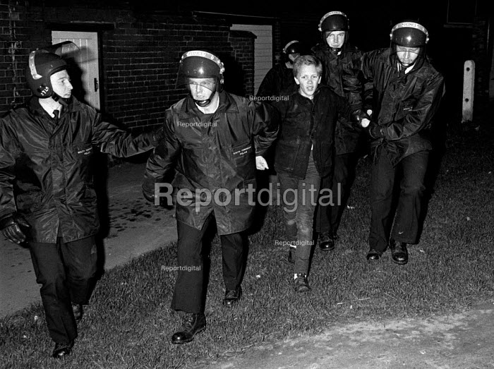 Police arrest a 13-year-old boy for throwing stones at a police convoy entering the village, Grimethorpe, Yorkshire - John Harris - 1984-07-09