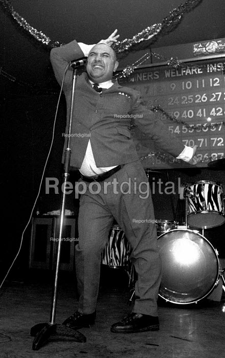 Stand-up comedian Alexei Sayle performing in a benefit gig for single miners at Christmas. Armthorpe Miners Welfare, miners strike Armthorpe, Doncaster, South Yorkshire - John Harris - 1984-12-13