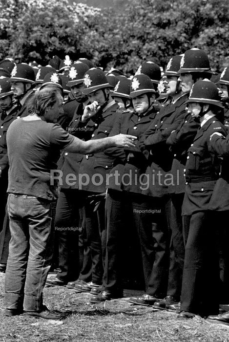 Picketing miner inspecting police lines arguing with an officer. Orgreave Coking works, South Yorkshire. - John Harris - 1984-06-03