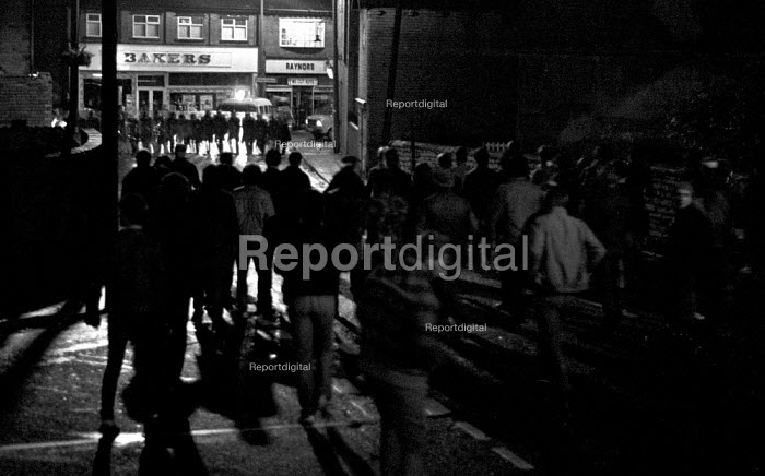 Pickets from Frickley confront riot police at night as they try to break the strike, the police were kept out of the village in a confrontation that went on all night. South Elmsall pit village, Yorkshire. - John Harris - 1984-11-15