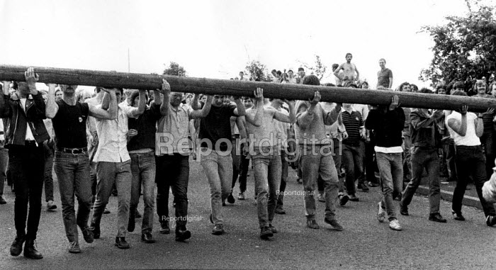 Pickets carrying a telegraph pole try to block the road to impead police charges by mounted and short shield riot police. Mass picket, Orgreave coke works, Yorkshire - John Harris - 1984-05-29