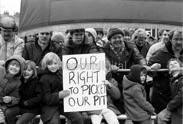 Miners, their wives and children march with their union banner to the pit. Picket of Frickley colliery in defiance of a court injunction limiting the number of pickets to 6, South Elmsall, Yorkshire. Miners strike. - John Harris - 1985-02-19
