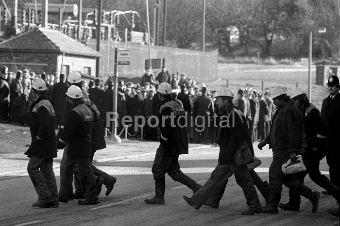 Some of the 27 scabs (out of 1200 miners) crossing the road from the washery as pickets look on, Silverwood colliery, Yorkshire - John Harris - 1985-02-15