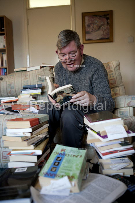 John, a disabled schizophrenic who hears voices, at home with his books which he reads avidly. His benefits have been reduced by the bedroom tax as his flat has a spare room. Stratford upon Avon, Warwickshire. - John Harris - 2014-03-08