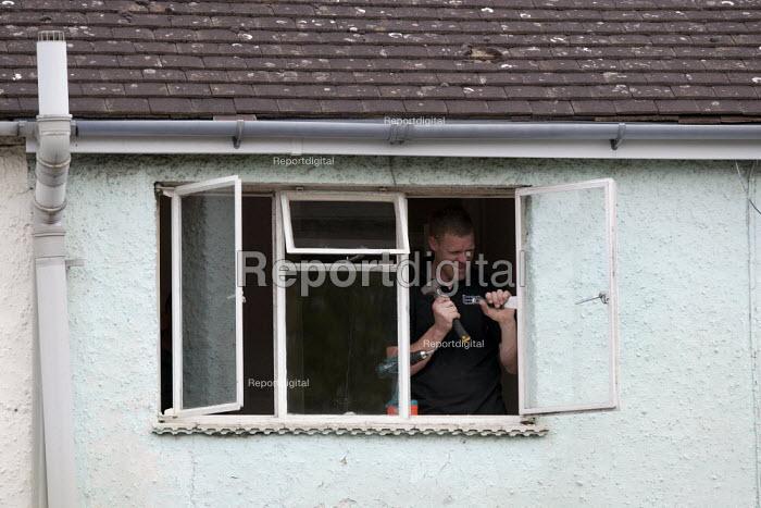 A Glazier fitting double glazing to a window. - John Harris - 2014-04-29