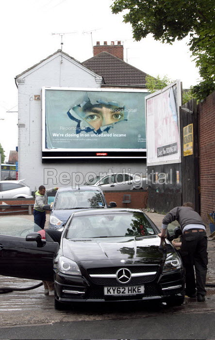 By hand car wash with a billboard advertisement for HM Revenue and Customs Tax, Were Closing In On Undeclared Income, If you have declared all your income you have nothing to fear - an evasion and benefit fraud poster intended to frighten the public into declaring all earnings, Coventry - John Harris - 2014-05-31