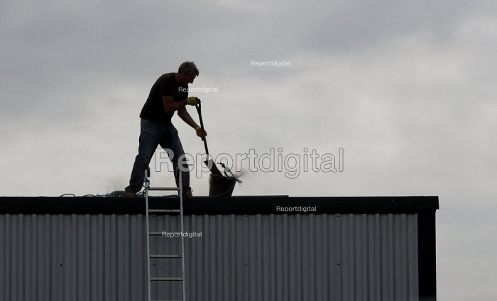 A worker clearing a industrial unit roof of debris, without a safety harness. - John Harris - 2014-07-11