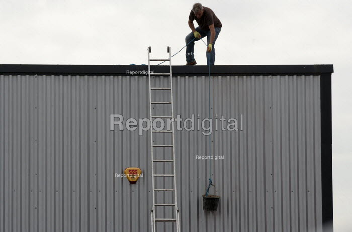 Lowering a bucket - a worker clearing a industrial unit roof of debris, without a safety harness. - John Harris - 2014-07-11