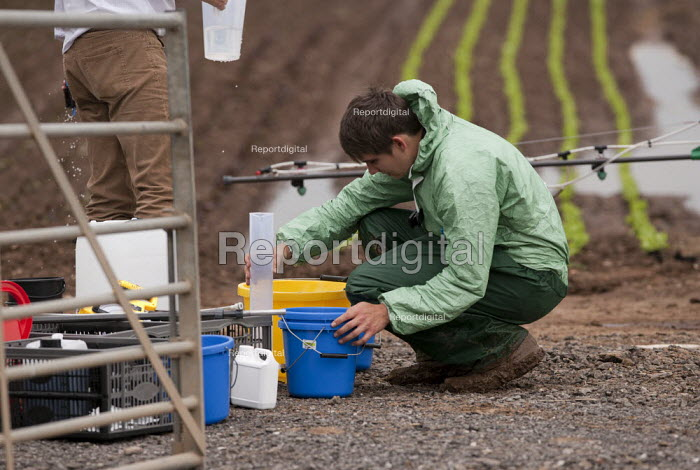 A farmworker wearing protective clothing (Waterproof Spray Suit) training in the use of a backpack Pesticide applicator, Warwickshire - John Harris - 2014-07-11