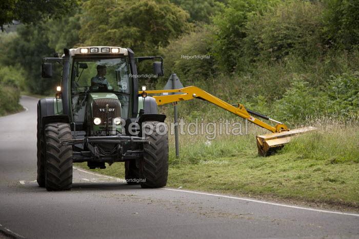 Farmworker cutting back roadside vegetation with a hedge cutter, Warwickshire - John Harris - 2014-07-11