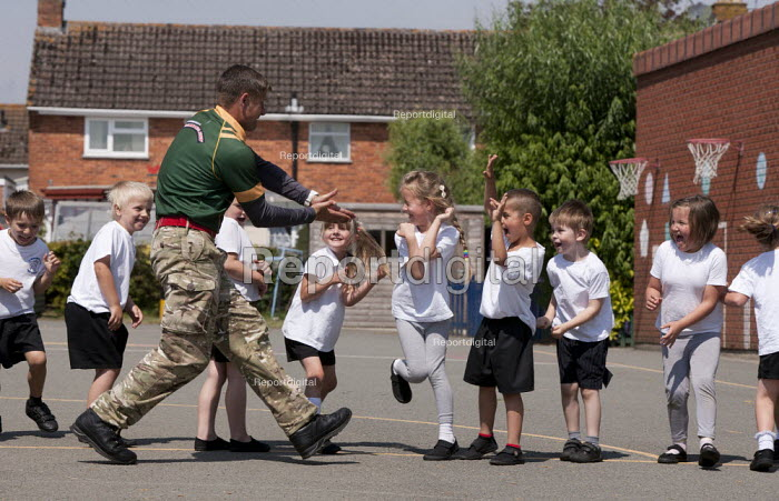 Commando Joe, a crocodile comes down the line; wake and shake and initiative to improve attendance and punctuality by working with an ex member of the armed forces, lining up in the playing field, St Richard's C E First School, Evesham - John Harris - 2014-07-02