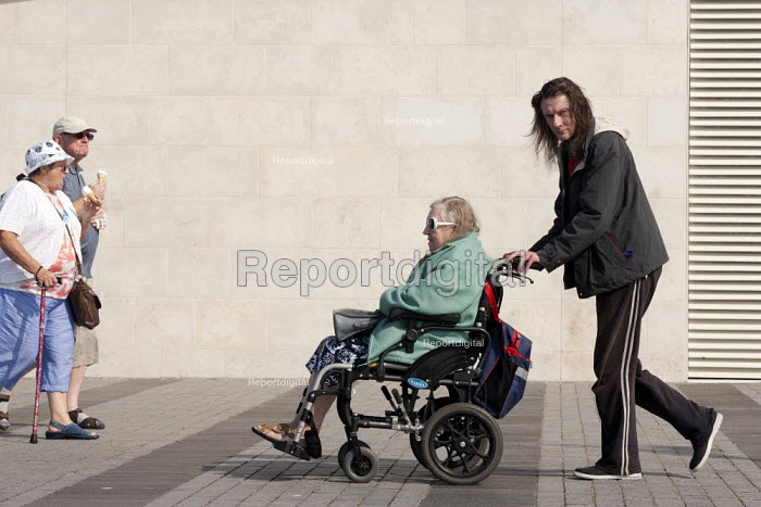 A carer pushing his elderly disabled mother, Liverpool 2014 - John Harris - 2014-09-10