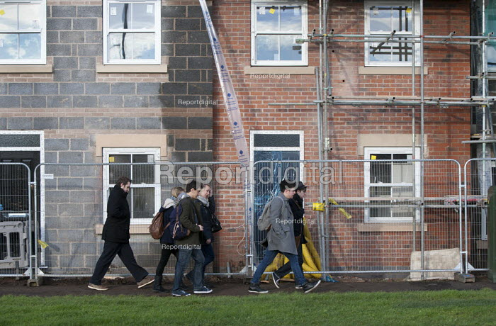 Students walking to college past new housing nearing completion which they may never be able to afford, Stratford-upon-Avon, Warwickshire - John Harris - 2014-12-18