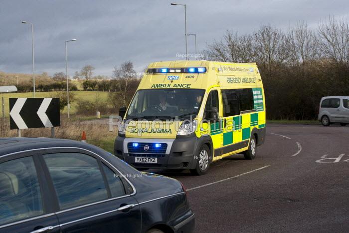 An ambulance on an emergency callout with its blue lights flashing speeds through traffic, Stratford-upon-Avon, Warwickshire - John Harris - 2014-12-18