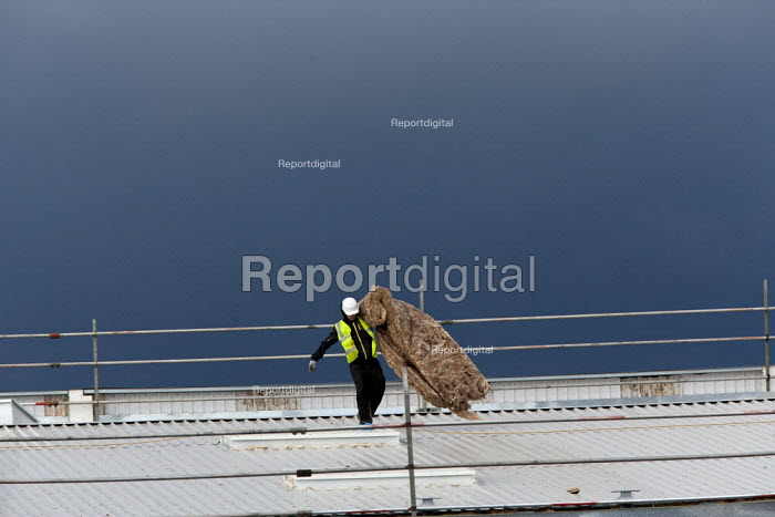 Construction worker with insulation on the roof of a new development, Wellesbourne Distribution Park, Warwickshire - John Harris - 2014-12-18