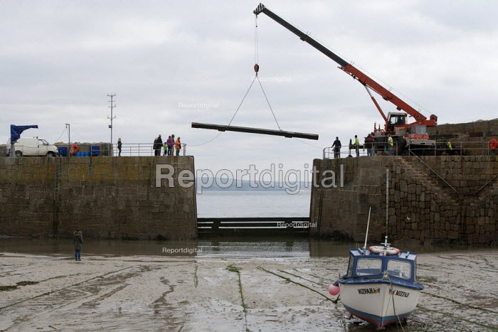 Crane lifting The Baulks which block the entrance to the harbour and provide protection against winter storms, Mousehole harbour, Cornwall - John Harris - 2015-03-22