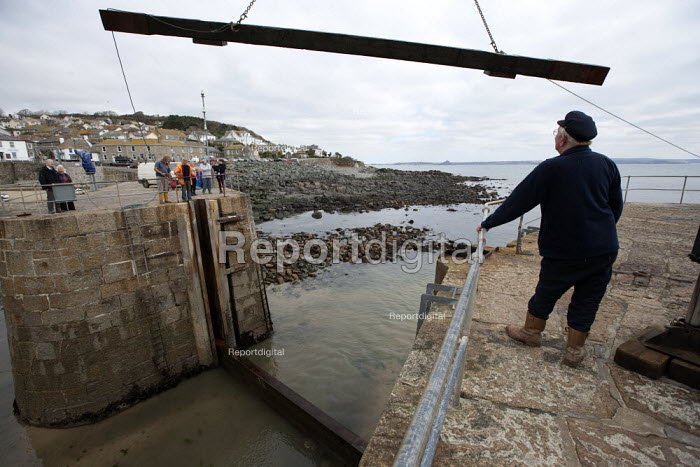 Harbour Master watching crane lifting The Baulks which block the entrance to the harbour in winter, Mousehole harbour, Cornwall - John Harris - 2015-03-22