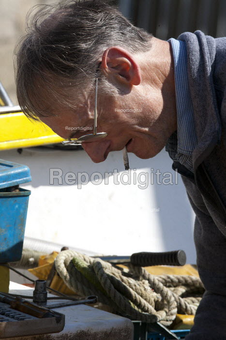 Fishermen repairing an engine of a fishing boat, Mousehole harbour, Cornwall - John Harris - 2015-03-22