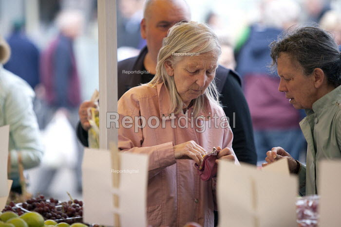 An elderly women finding the money from her purse to make a purchase from a market stall, Loughborough, Leicestershire - John Harris - 2015-04-25