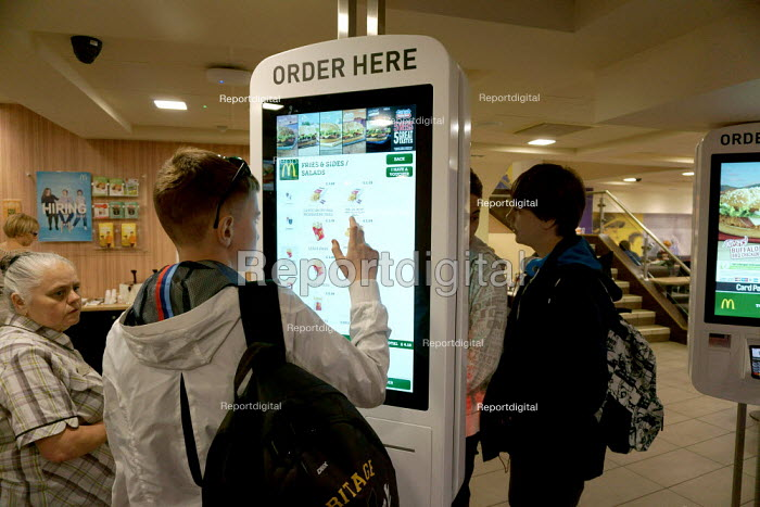 Customers ordering food using a digital kiosk with a touchscreeen menu, McDonald's restaurant, Stratford Upon Avoned, reproduced, manipulated or transmitted by any means without permission. - John Harris - 2015-05-30