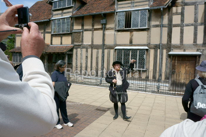 A Tourist Guide talking to a group outside Shakespeare's Birthplace, a guided walk around the historic streets of Stratford Upon Avon. - John Harris - 2015-05-30