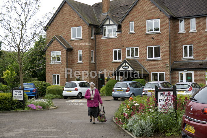 A resident walking into town from retirement flats in sheltered housing, Stratford Upon Avon, Warwickshire - John Harris - 2015-06-02